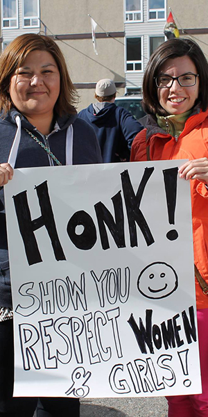 two women holding walk a mile HONK sign