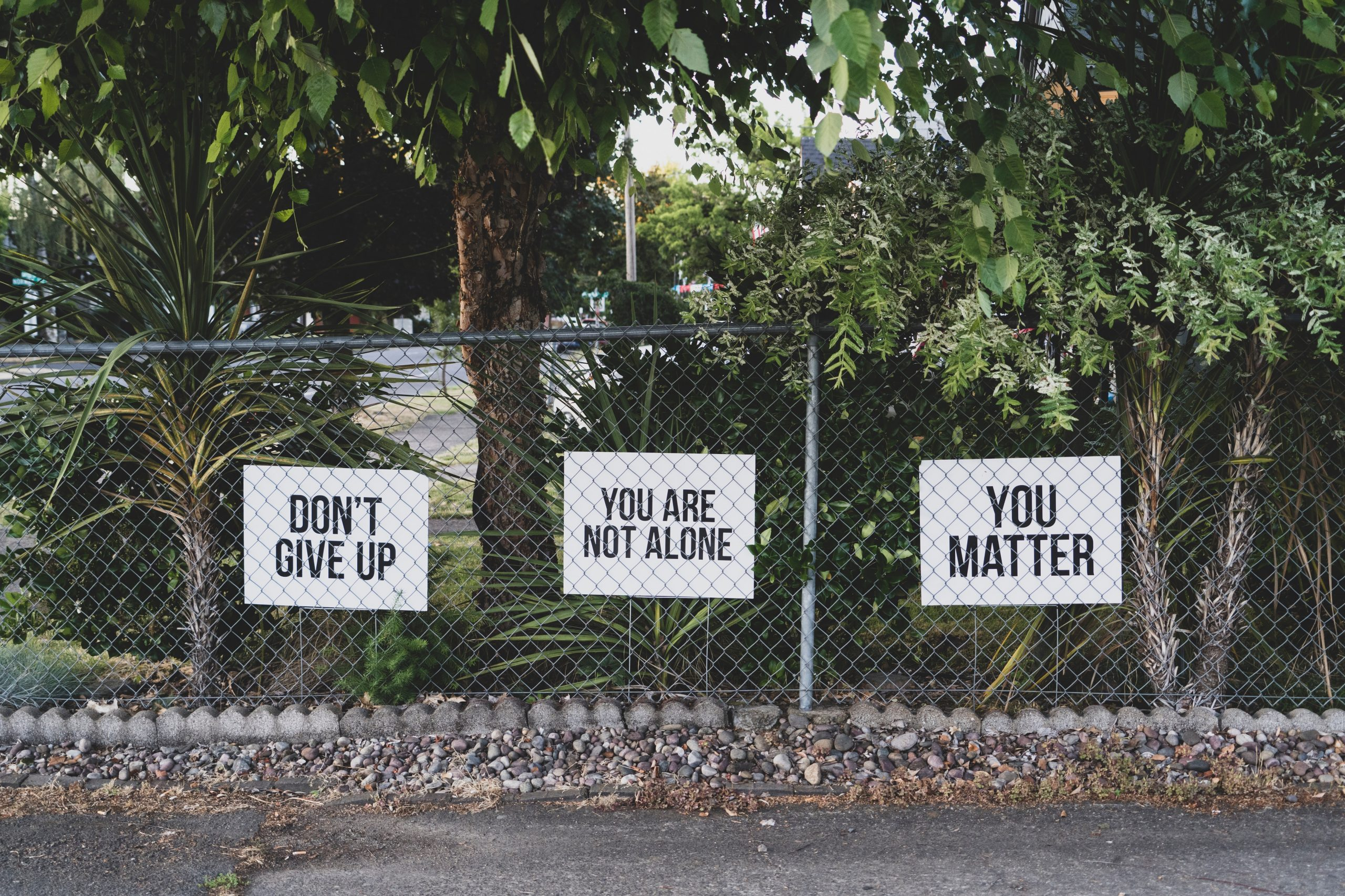 sign on fence - don't give up, you are not alone, you matter