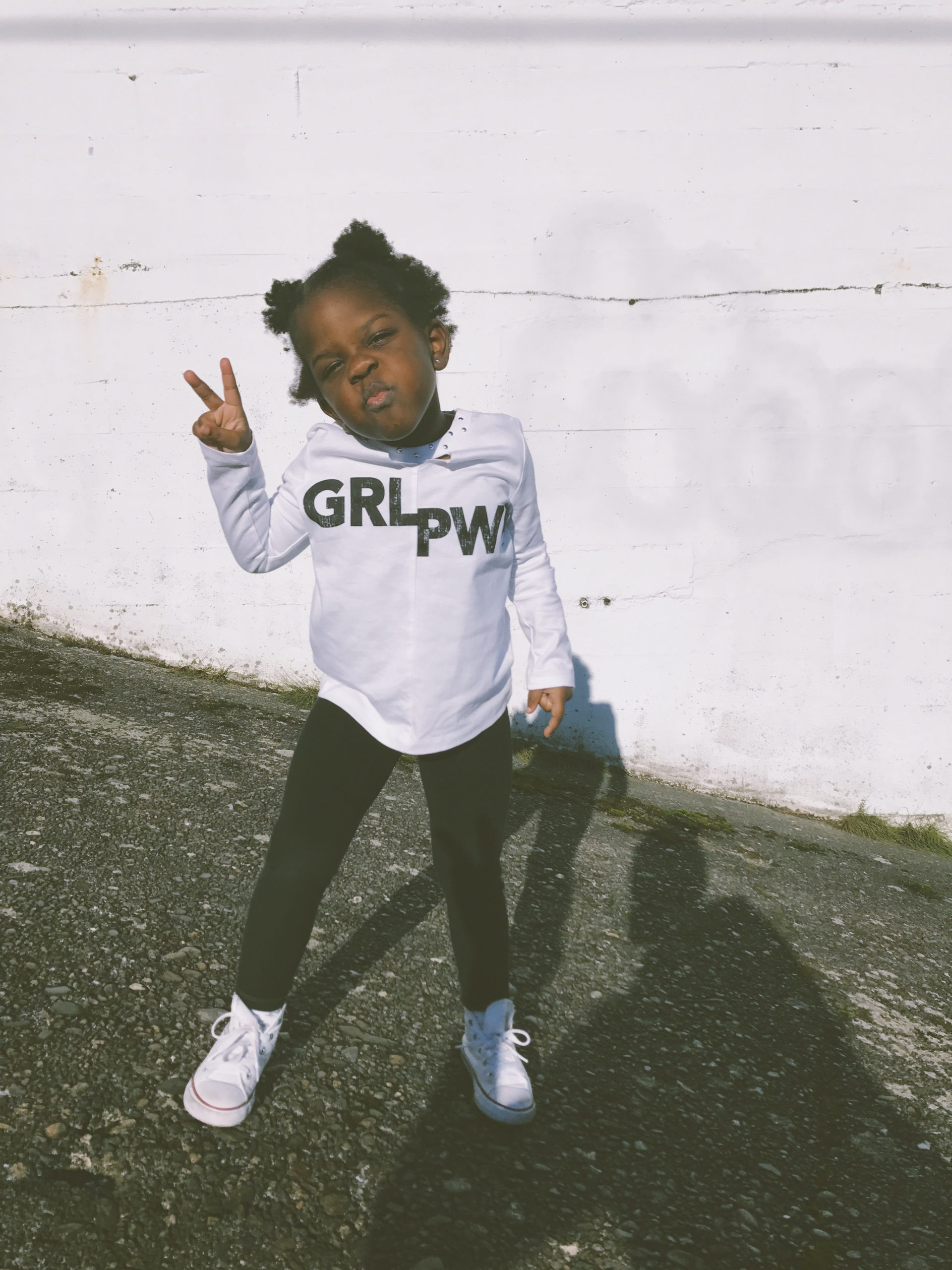 young girl giving peace sign with GRL PWR on shirt